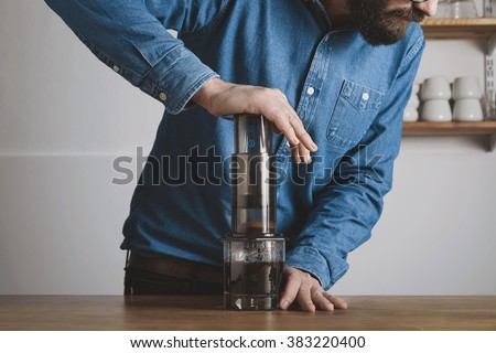 Step by step aero press coffee preparation Bearded barista in blue jeans shirt press aeropress to fill glass with beverage Professional coffee brewing cafe shop