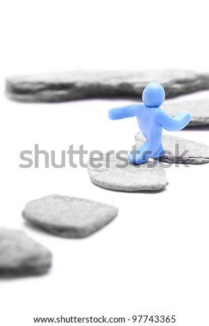 step by step to a higher level - blue plasticine guy jumping over stepping stones - career concept - isolated on white - stock photo