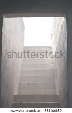 Step Into The Light. Dark stone hallway with a upward staircase leading into the sunlight. - stock photo