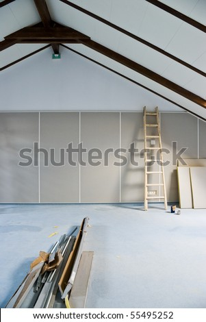 step ladder and construction materials in empty attic room - stock photo