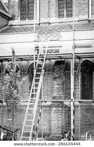 Step ladder resting against scaffolding conceptual monochrome image - stock photo