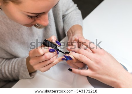 Step of manicure process nail covering with gel polish or shellac. Hand girl lying on the apparatus for drying the shellac or Uv lamp in spa beauty salon.
