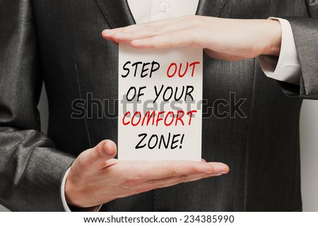 Step out of your comfort zone! Challenge concept in businessman hands - stock photo