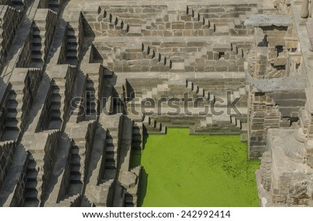 Step wells in Rajasthan India with zigzagging stairs down to the bottom to get water covered with green moss and lichen