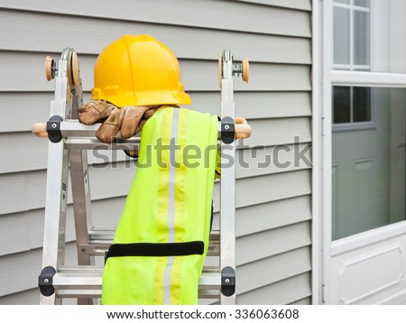 Stepladder with hardhat, work gloves, and reflective safety vest  - stock photo