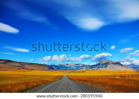 Steppes of Patagonia. Dirt road passes between the plains to the distant mountains - stock photo