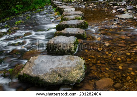 Stepping stones over river and small waterfall. - stock photo