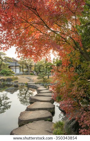 Stepping Stones Paths (roji) in Koko-en Garden is a Japanese garden in Autumn Red Maple Leaf Foliage located next to Himeji Castle in Hyogo Prefecture, Japan. Japanese style pond with Koi - stock photo