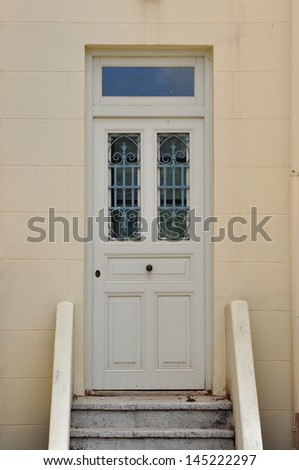 Steps and wooden door with vintage wrought iron pattern. Architectural detail.