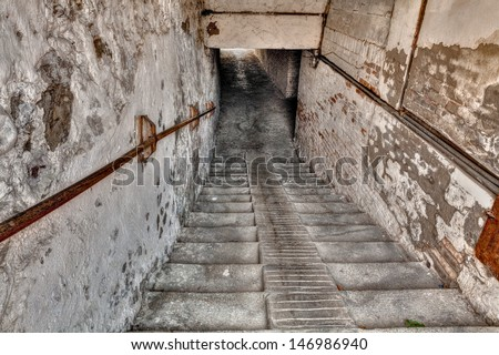 steps down to the underpass - descent with stairs to a narrow dark gallery in the old italian town - stock photo