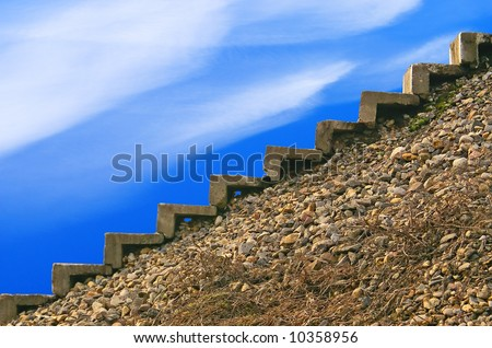 Steps of an old ladder on an abrupt stony slope, the bright dark blue sky, light easy plumes clouds.