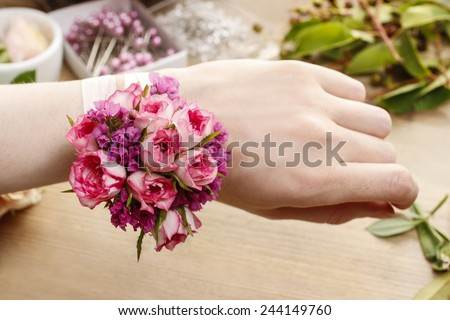 Steps of making wrist corsage. Florist at work. Woman making beautiful bouquet of pink roses. - stock photo