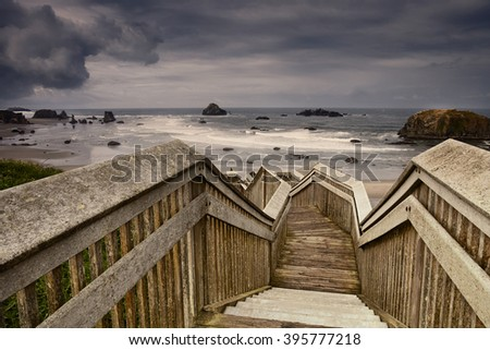Steps to the beach with storm clouds above