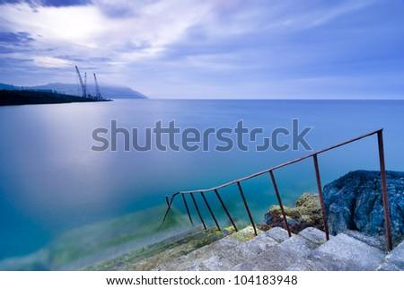 Steps to water, long exposure shot of Irish Sea bay, Greystones, Ireland - stock photo