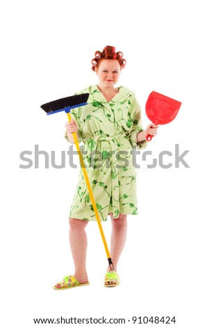 stereotypical houswife with hair rollers holding broom and scoop on white background - stock photo