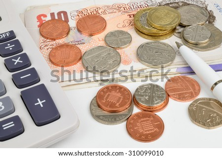 Sterling notes and coins, with a calculator and pen.