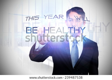 Stern asian businessman pointing against white room with large window overlooking city - stock photo