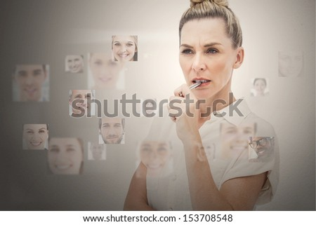 Stern businesswoman encircled by digital interface showing faces - stock photo