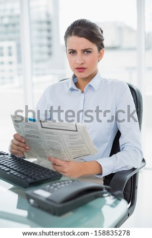 Stern classy brown haired businesswoman reading a newspaper in bright office