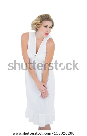 Stern fashion blonde model looking at camera on white background - stock photo