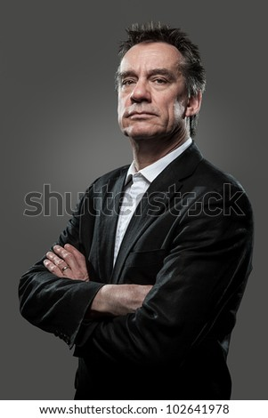 Stern Imposing Business Man with Arms Folded in Suit on Grey Background Grunge Look - stock photo