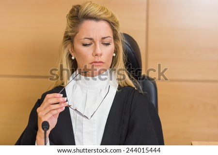 Stern judge looking and listening in the court room - stock photo
