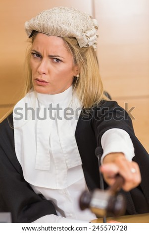 Stern judge pointing her hammer in the court room - stock photo