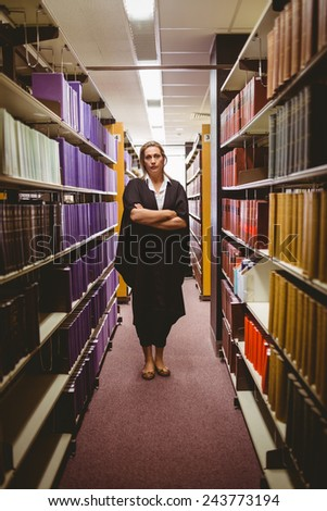 Stern lawyer standing between shelfs with arms crossed in library - stock photo