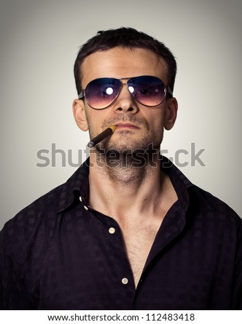 Stern man in sunglasses with a cigar - stock photo