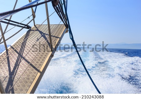 Stern of a ship while sailing between different islands, with views of the sea agitated by its own engine.