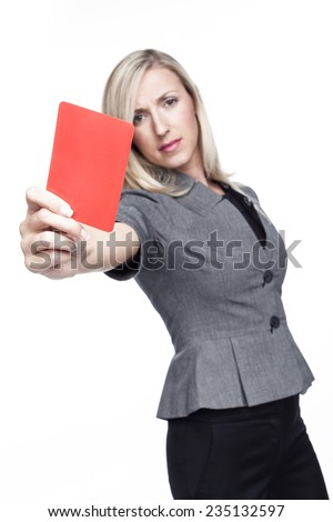 Stern young woman or referee in a stylish grey top showing a red card to send a player off the field or out of the game, isolated on white