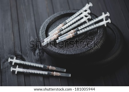 Steroids - syringes and dumbbell weight plates, studio shot - stock photo