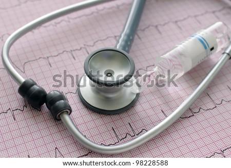 Stethoscope, ampoule on surface ECG. Medical background. - stock photo