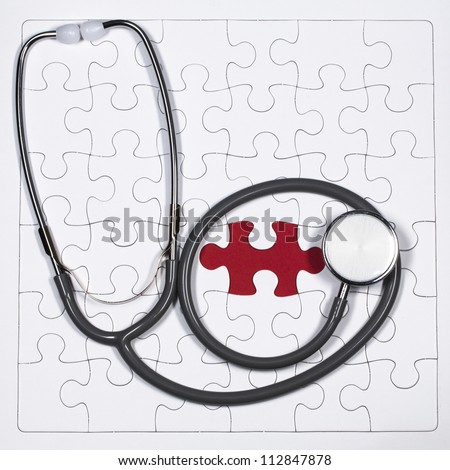 Stethoscope and a jigsaw puzzle - stock photo