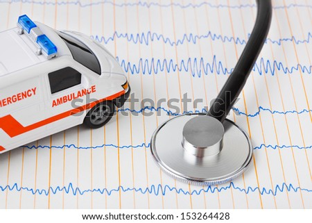 Stethoscope and ambulance car on ecg - medical background - stock photo