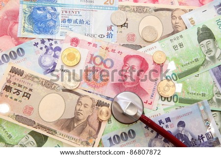 stethoscope and Background of asian currency (include Korean Won, Taiwan dollar, Chinese Money yuan , Hong Kong Dollar, japanese Yen) - stock photo