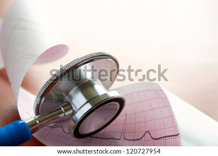 stethoscope and cardiogram on the table - stock photo
