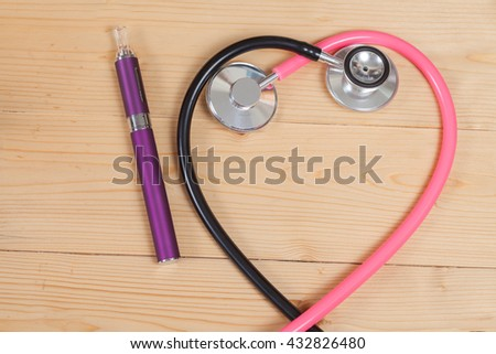 stethoscope and e- cigarette on wood table