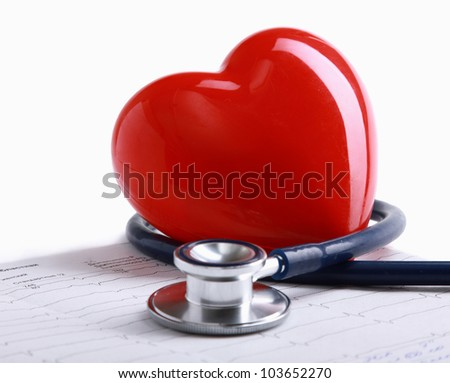 Stethoscope and heart on the diagramm - stock photo