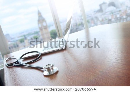 stethoscope and laptop computer on wood table and london big ben blurred background copy space   - stock photo