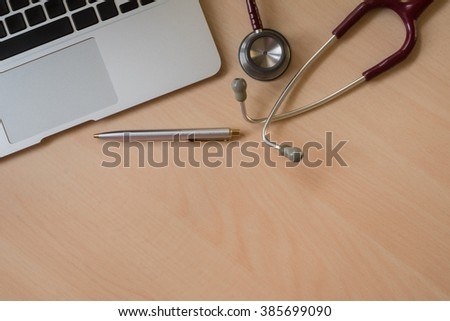 Stethoscope and laptop keyboard on wooden desktop with space for text
