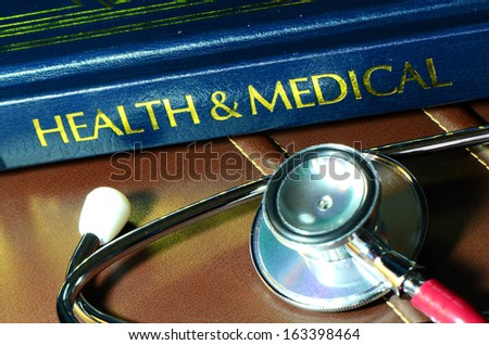 Stethoscope and medical text book on the doctor's desk. - stock photo