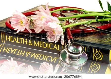 Stethoscope and medical text book with reflection on the doctor's desk isolated with clipping path. - stock photo