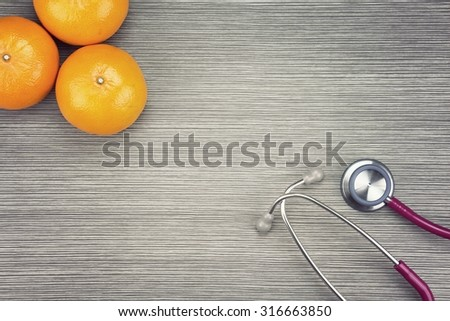 Stethoscope and orange on a wooden background. Medical equipment, Healthy food, Healthy eating concept. (Vintage Style Color) - stock photo