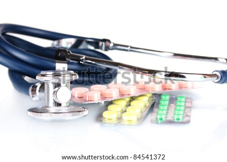 stethoscope and pills isolated on white