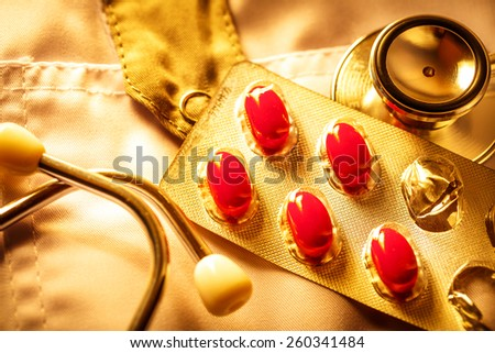 Stethoscope and pills on doctor's smock in toning - stock photo
