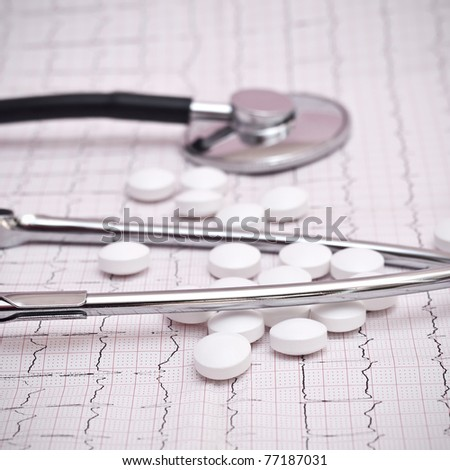stethoscope and pills on ecg - stock photo