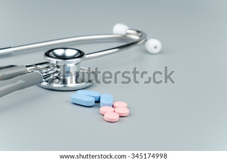 Stethoscope and pills on grey background, medical concept  - stock photo