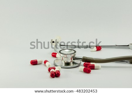 Stethoscope and pills on white background