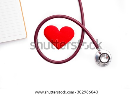 Stethoscope and red heart and notebook on white background - stock photo